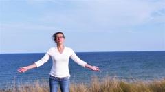 4K. Adult woman meditates against sea surface Stock Footage