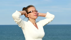 4K.Adult woman in spectacles with raised hands against sea surface Stock Footage