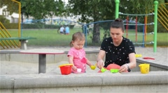 Mother and baby daughter playing and making shapes in the sandbox, beautiful Stock Footage