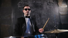 Man in black suit and sunglasses plays on drum. Rock cover band performing on - stock footage