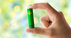 Close up of hand holding green alkaline battery Stock Photos