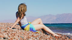 Young woman sitting on tropical beach in Egypt Stock Footage