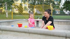 Charming family of two playing and making shapes in the sandbox on a summer day - stock footage