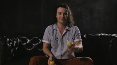 Person in studio juggles apples and smiles to camera Stock Footage