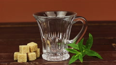 Tea being poured into glass tea cup and brown sugar in cubes with mint leaves on Stock Footage