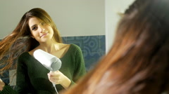 Gorgeous lady blow drying long hair in bathroom looking camera slow motion Stock Footage