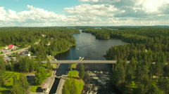 Aerial Shot of Bridge over River Surrounded by Pine Forest.  Stock Footage