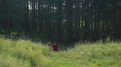 Couple walking together and holding hands in forest and shadows all around. Stock Footage