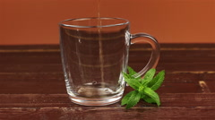 Tea being poured into glass tea cup and mint leaves on brown wooden table Stock Footage