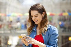 Young brunette woman reading a message on the phone Stock Photos