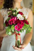 Close up of wedding bouquet of bridal flowers in hands of anonymous bride Stock Photos