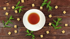 Sugar cubes added into tea glass on table with fresh mint leaves and brown sugar Stock Footage