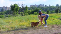 Two girls female playing with friend american bulldog Stock Footage