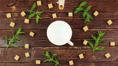 Tea being poured into glass tea cup on table with fresh mint leaves and brown - stock footage