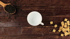 Tea being poured into glass tea cup on him located brown sugar and spoon with Stock Footage