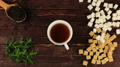 Sugar cubes added into tea glass on him located brown and white sugar cubes Stock Footage