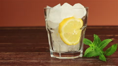 Glass of ice tea with mint and lemon, ice cubes on brown wooden table Stock Footage
