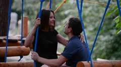 In love couple in the park on a wooden swing Stock Footage