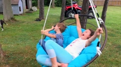 Boy and Girl Spinning Wildly In Outdoor Swing Stock Footage