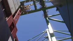 Container ship being unloaded by crane ship to truck Stock Footage