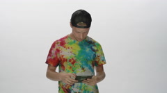 Hippy guy with tie dyed t-shirt using social media on smart device - stock footage