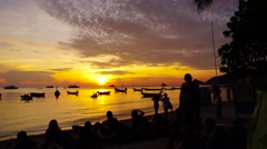 Sunset time lapse with people on the beach and boats Stock Footage