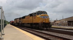 Yellow freight train pulling into station in southern texas, wide shot Stock Footage