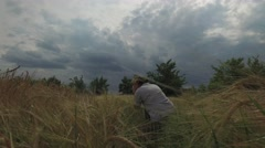 Woman sat down and photographed field of wheat Stock Footage