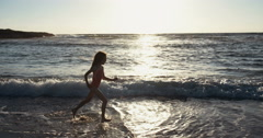 Silhouette of a girl running  happy on the beach Stock Footage