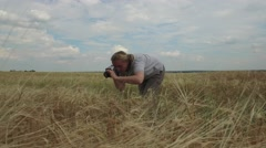 Woman photographs wheat ears on background of blue cloud Stock Footage