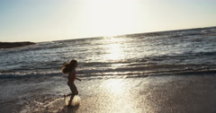 Young girl running at the beach playing with the waves - stock footage