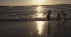 Three kids playing together at the beach Stock Footage