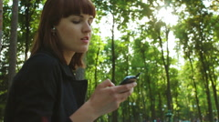 Girl Sitting and Listing to Music in the Park Stock Footage