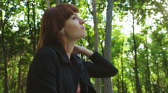 Girl Sitting and Listing to Music in the Park - stock footage