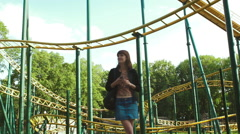Girl Waiting for here Friend and Listing to Music in the Amusement Park - stock footage