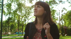 Girl Walking and Listing to Music in the Park - stock footage