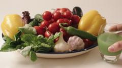 Hand puts juice against fresh vegetables on  plate Stock Footage