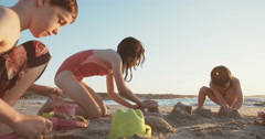 Children cuilding sand castles during sunset on the beach Stock Footage
