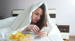 Girl eating chips in bed and watching news in phone Stock Footage