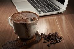 Full cup of coffee spilled Stock Photos