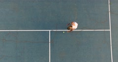 Professional tennis player taking the tennis ball and serving. Overhead shot Stock Footage