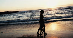 Silhouette of a Woman and young doughter running on the beach together Stock Footage