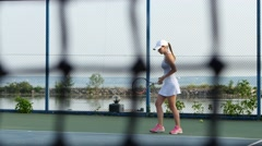 Tennis net and woman playing tennis in the background. Dolly shot Stock Footage