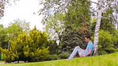 University student studying for exams outdoors in the park. With him his books Stock Footage