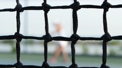 Girl tennis player expecting the tennis ball on court, net in front. Dolly shot Stock Footage