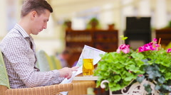 Caucasian young european man with citymap in outdoors cafe. Portrait of Stock Footage