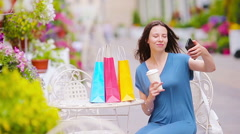Fashion happy girl with bags after shopping taking selfie in openair cafe. Sale Stock Footage