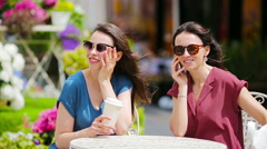 Two young girls using smart phone at the outdoors cafe. Two women after shopping Stock Footage