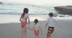 Steadicam shot of three kids running to the ocean - stock footage
