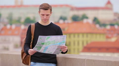 Man tourist with a city map and backpack in Europe. Caucasian boy looking with Stock Footage